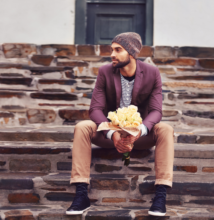 Shot of a handsome young man holding a bunch of flowers while waiting on the steps